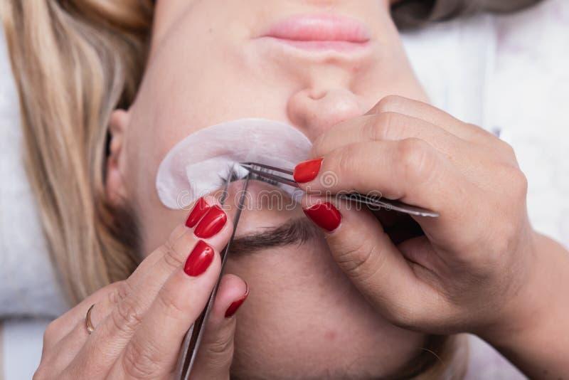 Uitbreidingsprocedure met Eyelash Vrouw Oogje met Lange valse Eyelashes macro-shot van modeogen in schoonheidssalon stock foto's