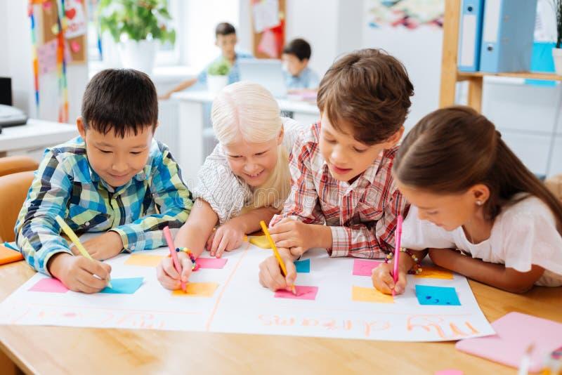 Uitbundige kinderen die een affiche in een klaslokaal trekken royalty-vrije stock afbeeldingen