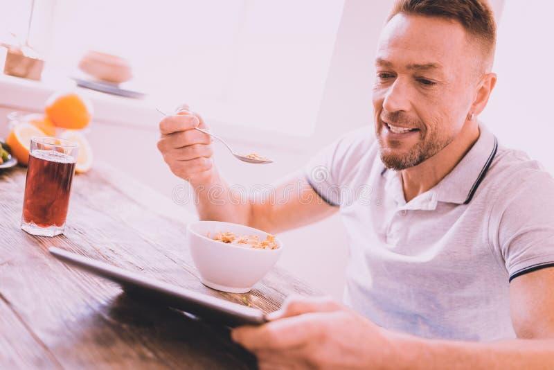 Uitbundige knappe mens die graangewassen thuis eten royalty-vrije stock foto