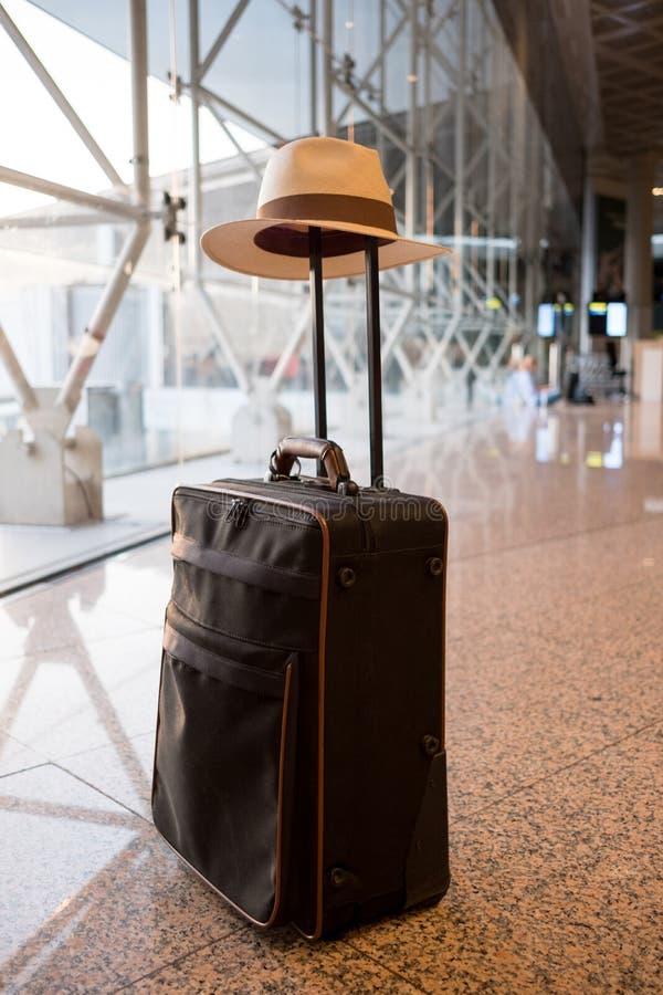Uitcase con el sombrero del verano en el aeropuerto fotos de archivo