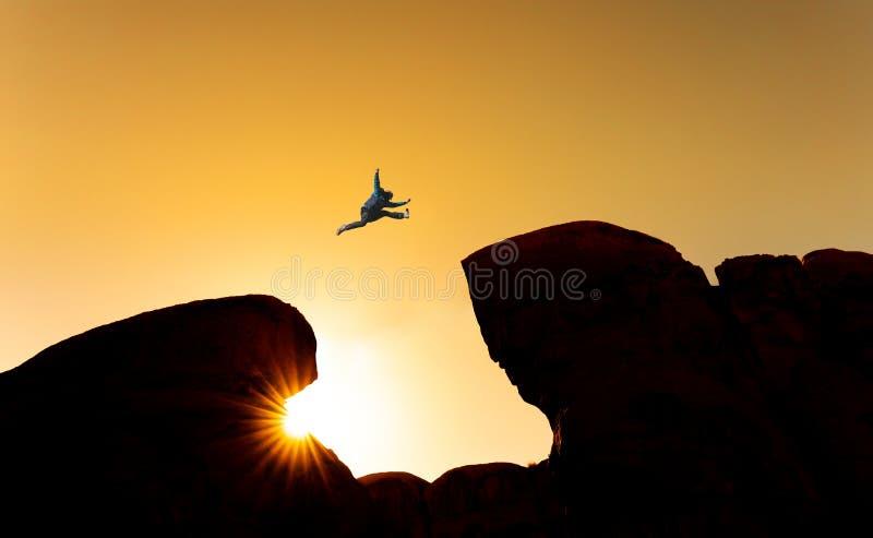 Uitdaging, risico en vrijheidsconcept Silhouetteer een mens die over afgrond springen klip kruisen royalty-vrije stock foto