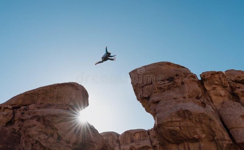 Uitdaging, risico en vrijheidsconcept Silhouetteer een mens die over afgrond springen klip kruisen royalty-vrije stock foto's