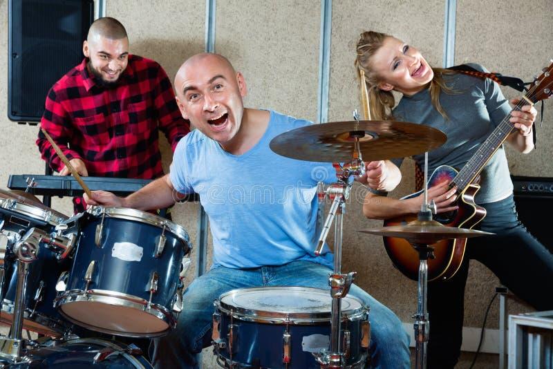 Uitdrukkende drummer met zijn bandmaten die oefenen in de repetitiezaal stock afbeelding