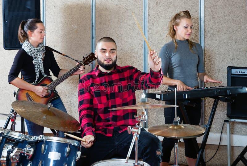 Uitdrukkende drummer met zijn bandmaten die oefenen in de repetitiezaal stock afbeeldingen