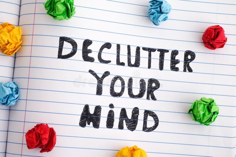 Uitdrukking Declutter Uw Mening op notitieboekjeblad met kleurrijke verfrommelde document ballen rond het royalty-vrije stock foto