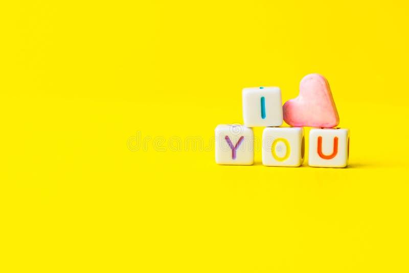 Uitdrukking I Liefde u construeerde van witte brievenkubussen en roze de suikersuikergoed van de hartvorm op heldere gele achterg royalty-vrije stock foto