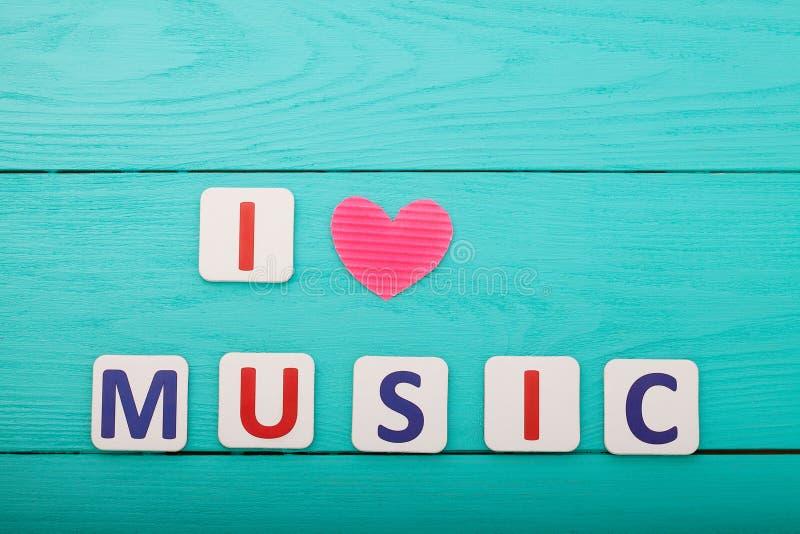 Uitdrukking I liefdemuziek op blauwe houten achtergrond Hoogste mening Spot omhoog stock afbeelding