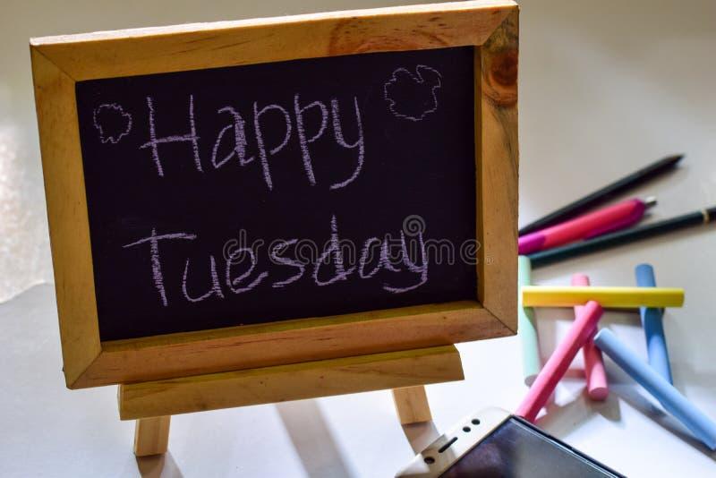 Uitdrukkings gelukkige die dinsdag op een bord op het en smartphone, kleurrijk krijt wordt geschreven royalty-vrije stock afbeelding
