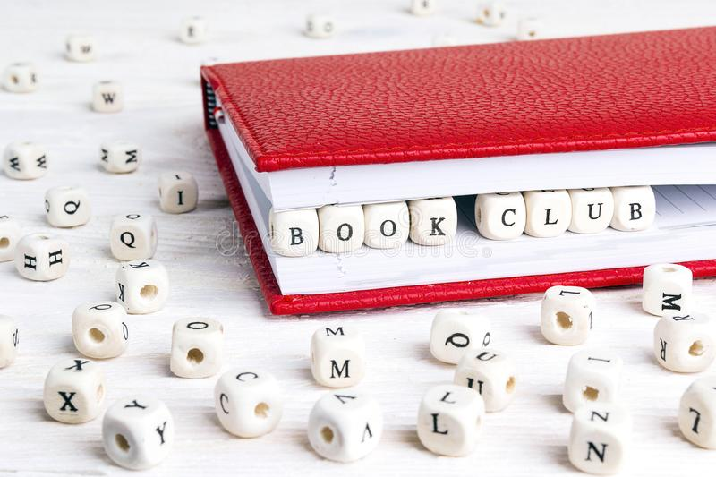 Uitdrukkingsboekenclub in houten blokken in rood notitieboekje op whi wordt geschreven die royalty-vrije stock fotografie