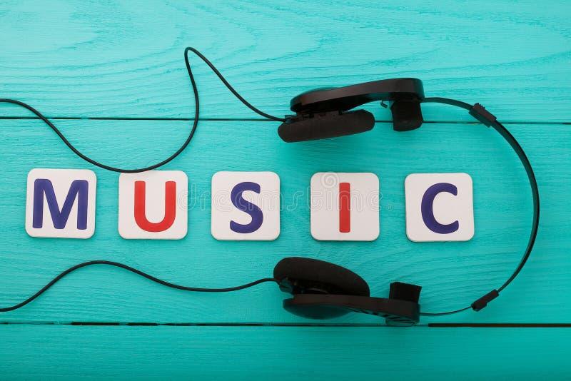 Uitdrukkingsmuziek met hoofdtelefoons op blauwe houten achtergrond Hoogste mening Spot omhoog De ruimte van het exemplaar royalty-vrije stock foto's