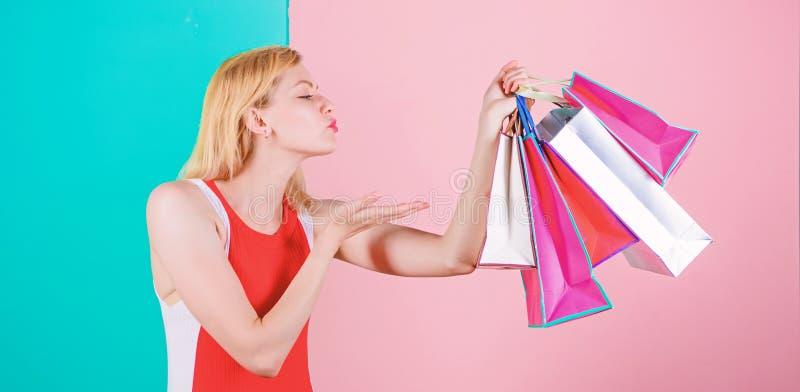Uiteinden om verkoop met succes te winkelen De greepbos van de vrouwen rode kleding het winkelen zakken blauwe roze achtergrond H stock afbeelding