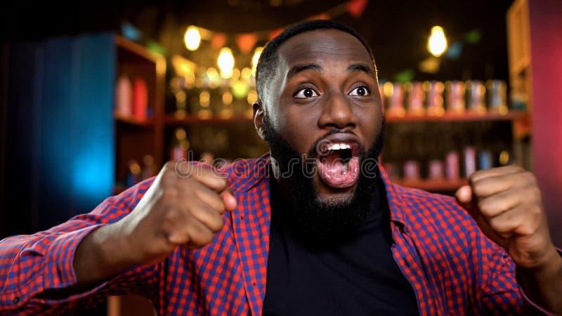 Uiterst gelukkige Afrikaans-Amerikaanse ventilator die favoriete teamoverwinning in bar vieren royalty-vrije stock fotografie