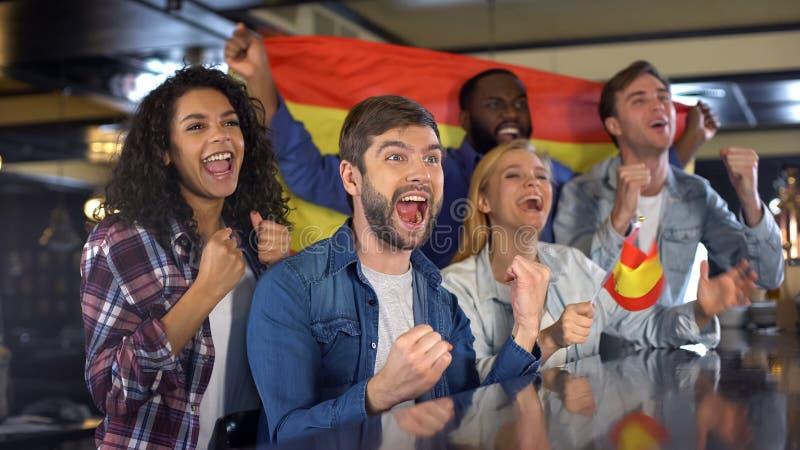 Uiterst gelukkige Spaanse verdedigers die nationale vlag golven, vierend overwinning royalty-vrije stock foto