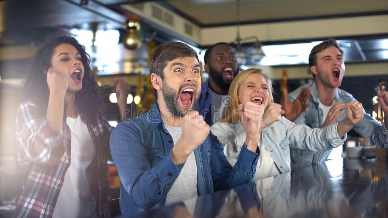 Uiterst gelukkige sportventilators die actief team toejuichen, die overwinning in bar vieren stock foto