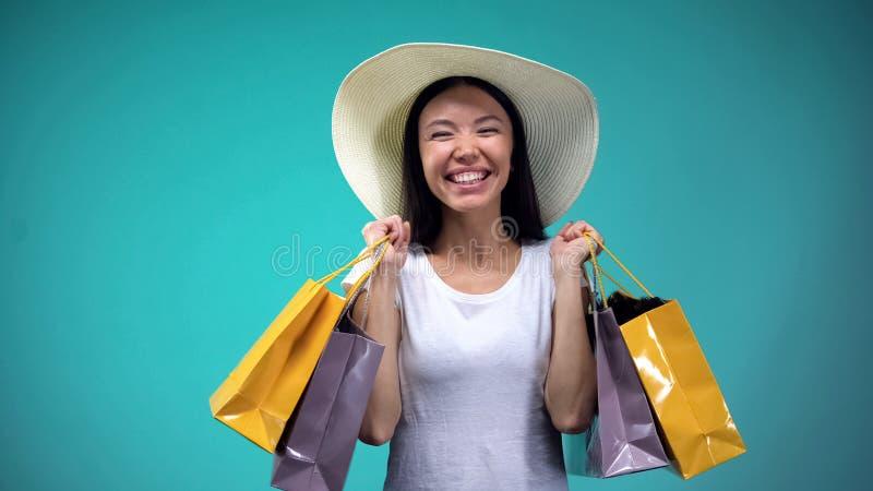 Uiterst gelukkige vrouw die in witte hoed vele document zakken, gewijd winkelen houden stock foto