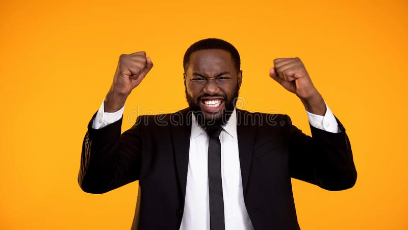 Uiterst gelukkige zwarte werknemer die en ja gebaar glimlachen maken, die bevordering krijgen royalty-vrije stock afbeeldingen