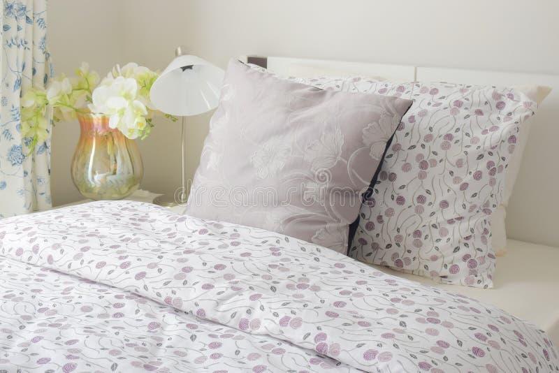 Uiterst klein de stijlbeddegoed van het lavendelpatroon in slaapkamer met witte orchidee naast bed royalty-vrije stock foto's