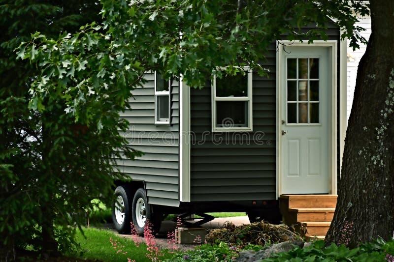 Uiterst klein grijs huis op wielenclose-up stock fotografie