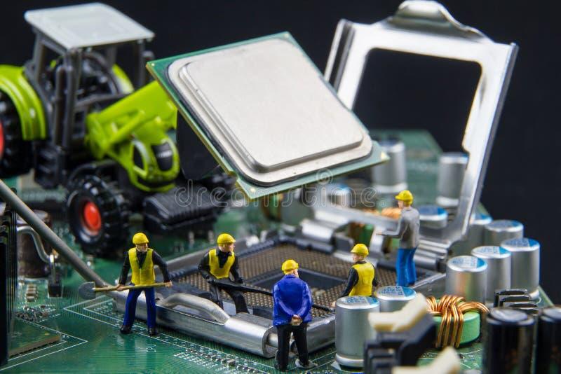 Uiterst klein speelgoedteam van ingenieurs die de raadscompu herstellen van de kringsmoeder stock afbeelding