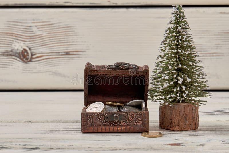 Uiterst kleine juwelendoos met muntstukken en Kerstmisboom stock afbeeldingen