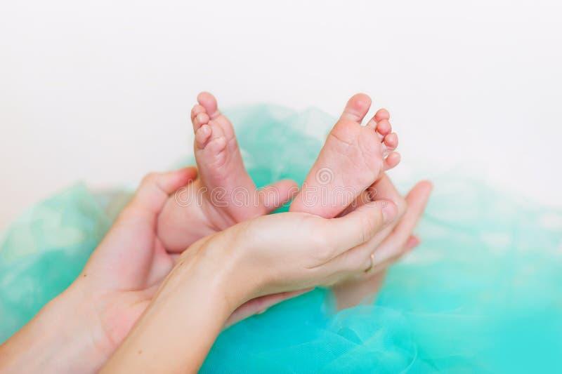 Uiterst kleine pasgeboren babyvoet in vrouwelijke handen, close-up Leuk weinig jong geitjebeen Moederschap, liefde, zorg, nieuw h royalty-vrije stock afbeeldingen