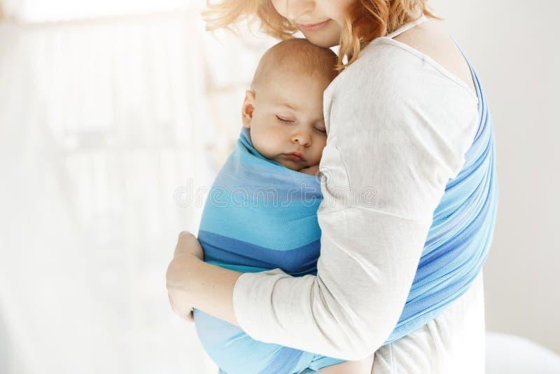 Uiterst kleine pasgeboren kind dichte ogen en het hebben van goede slaap in babyslinger die bescherming tegen zijn mooie jonge mo stock foto's