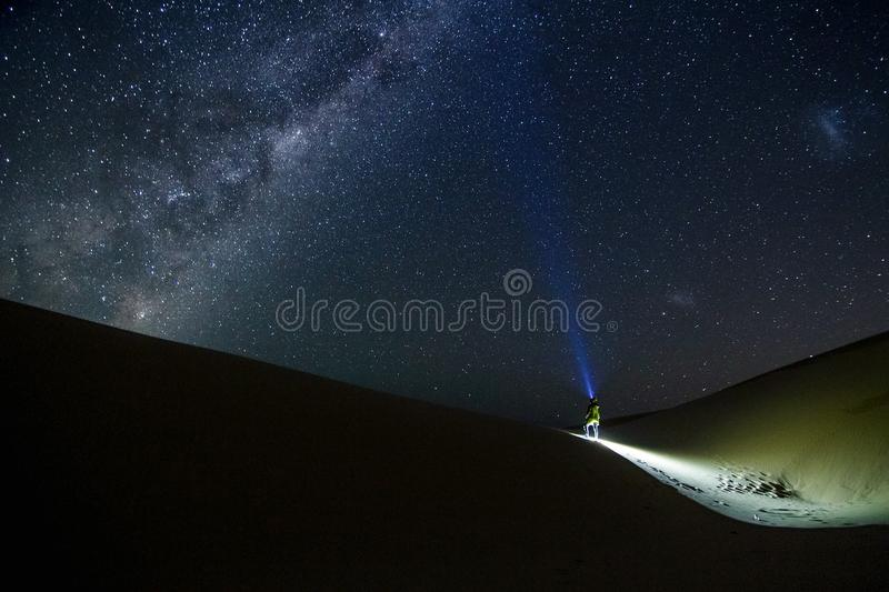 Uiterst kleine reizigers die lichten houden en op de reusachtige melkachtige manier letten stock foto's