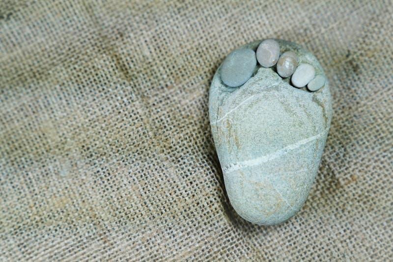 Uiterst kleine steenvoeten op juteachtergrond royalty-vrije stock foto's