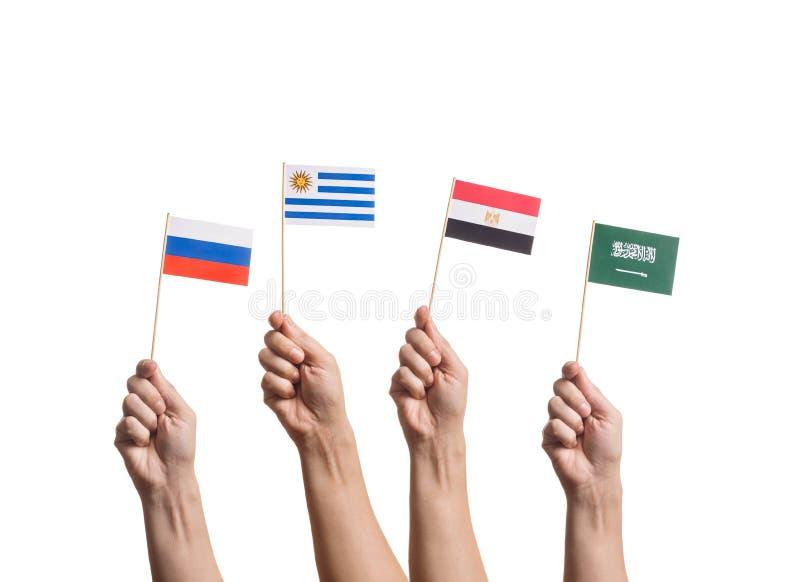 Uiterst kleine vlaggen in handen stock afbeelding