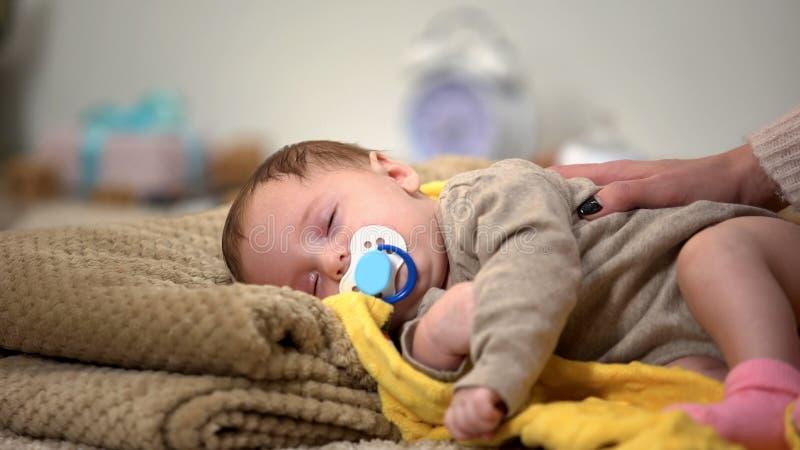 Uiterst leuke pasgeboren babyslaap die binky, gezonde kindontwikkeling zuigen stock fotografie