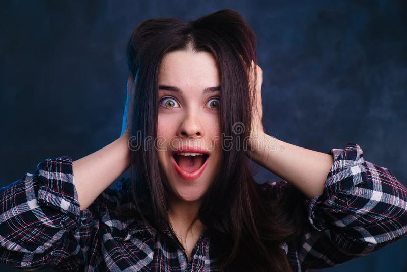 Uiterst verraste, opgewekte, geschokte jonge vrouw wat betreft haar h stock foto's