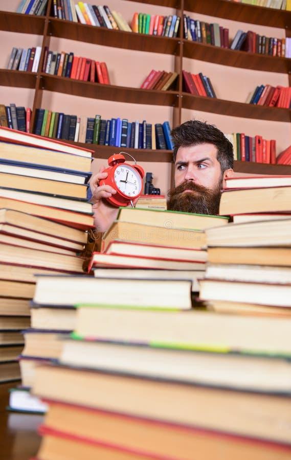 Uiterste termijnconcept Mens die op strikt gezicht klok, boekenrekken op achtergrond bekijken Leraar of student met baard het bes stock fotografie