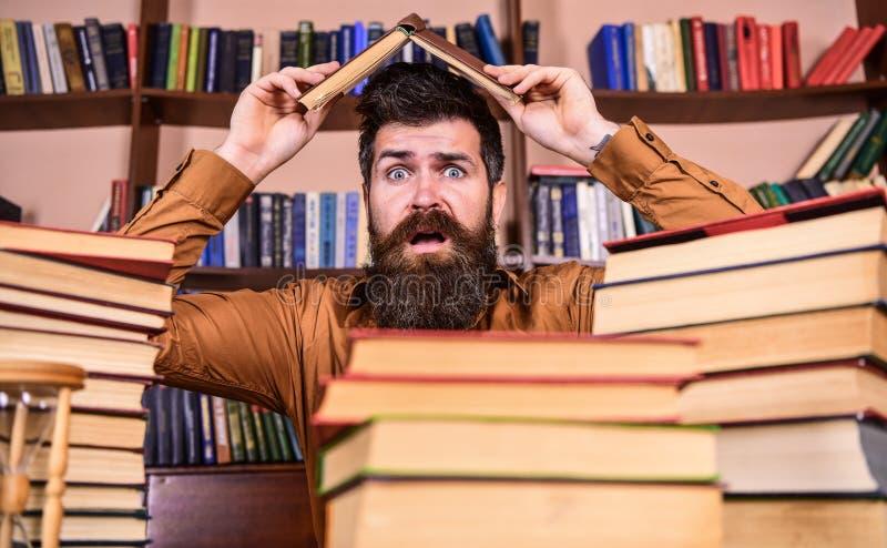 Uiterste termijnconcept Mens op geschokt gezicht tussen stapels van boeken, terwijl het bestuderen in bibliotheek, boekenrekken o royalty-vrije stock afbeelding