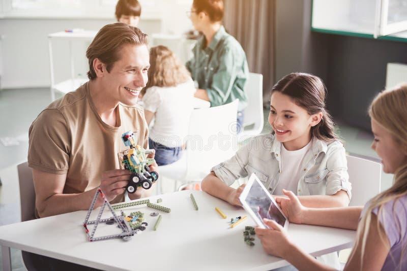Uitgaand leraar en jonge geitjesgokken met robot stock foto's