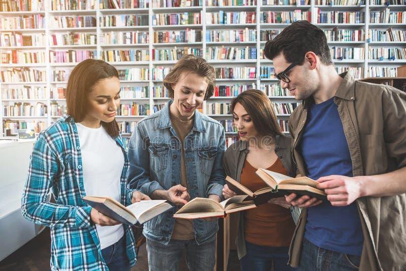 Uitgaande groupmates die boeken in bibliotheek lezen stock afbeelding