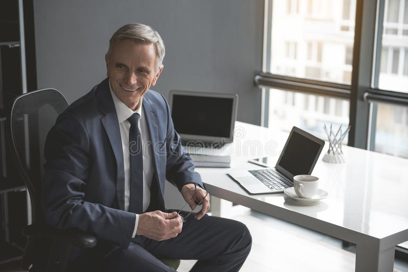 Uitgaande rijpe zakenman die in bureau werken stock foto
