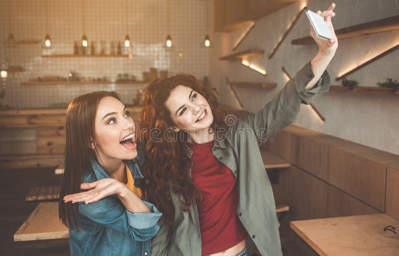 Uitgaande twee vrouwen die selfie op smartphone binnen maken stock afbeeldingen