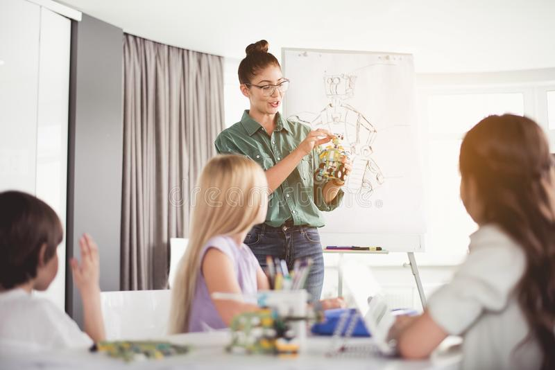 Uitgaande vrouw die jonge geitjes bestuderen die stuk speelgoed maken royalty-vrije stock afbeelding
