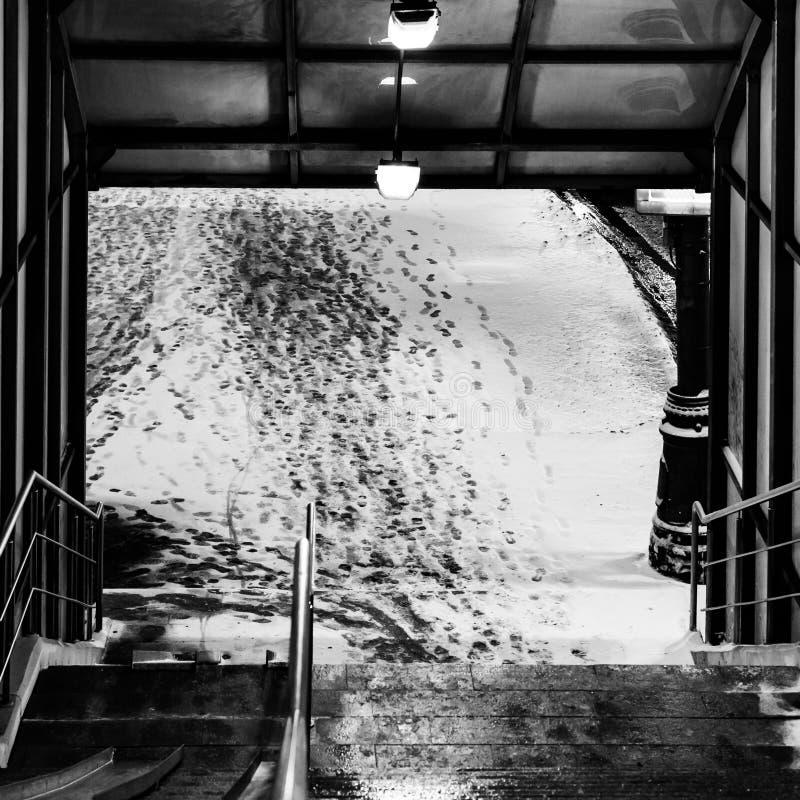 Uitgang van de voetgangersoversteekplaats Voetsporen in de sneeuw De winter conceptuele samenstelling stock fotografie