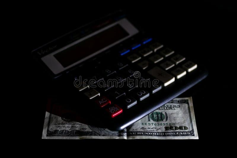 Uitgavenkosten, begroting en belasting of investeringsberekening, dollar honderd met calculator op donkere zwarte lijst als achte stock foto