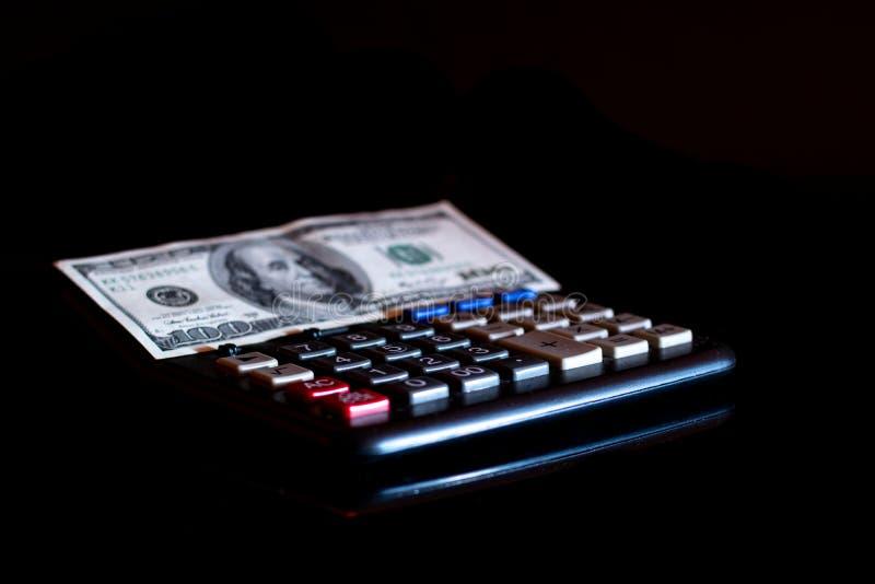 Uitgavenkosten, begroting en belasting of investeringsberekening, dollar honderd met calculator op donkere zwarte lijst als achte stock afbeelding