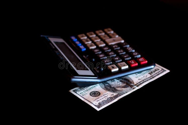 Uitgavenkosten, begroting en belasting of investeringsberekening, dollar honderd met calculator op donkere zwarte lijst als achte royalty-vrije stock afbeelding