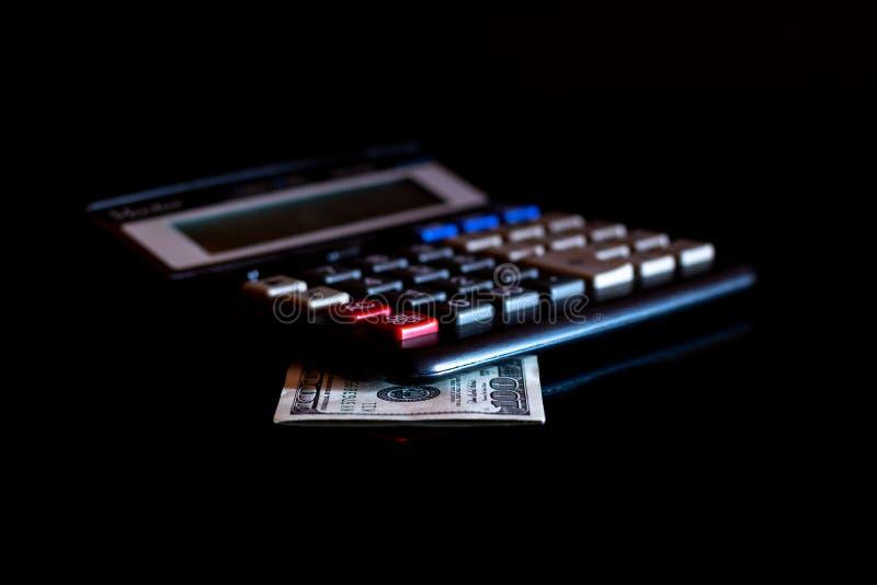 Uitgavenkosten, begroting en belasting of investeringsberekening, dollar honderd met calculator op donkere zwarte lijst als achte royalty-vrije stock foto