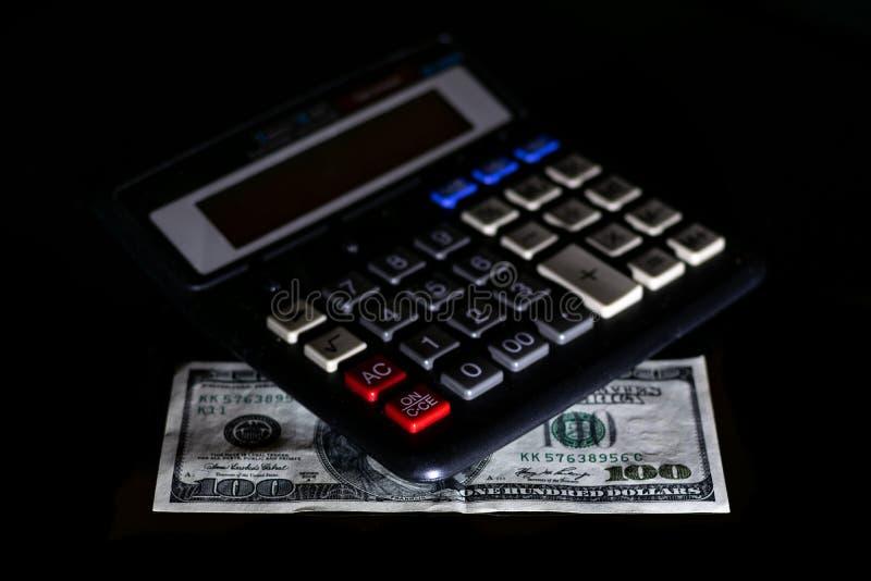 Uitgavenkosten, begroting en belasting of investeringsberekening, dollar honderd met calculator op donkere zwarte lijst als achte royalty-vrije stock foto's