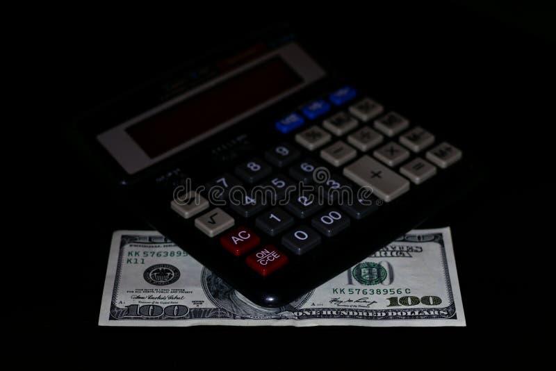 Uitgavenkosten, begroting en belasting of investeringsberekening, dollar honderd met calculator op donkere zwarte lijst als achte royalty-vrije stock fotografie