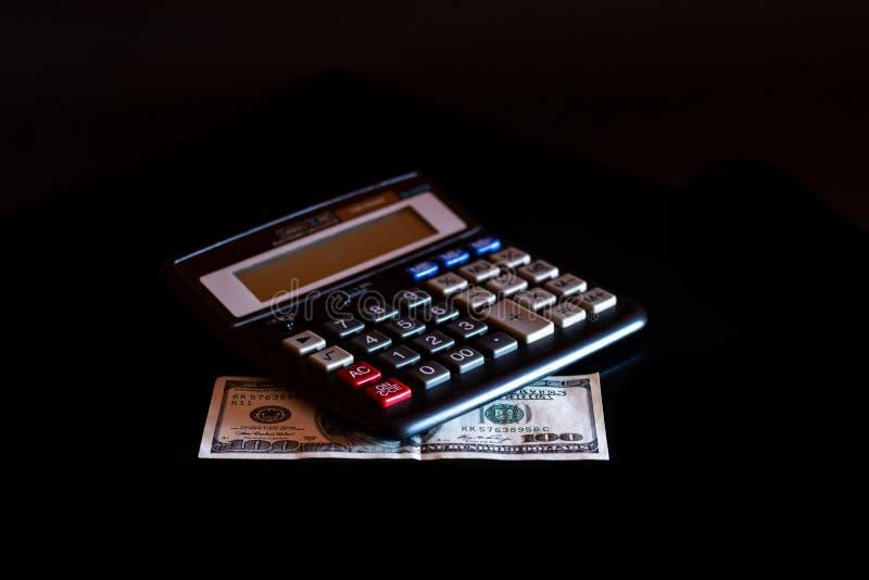 Uitgavenkosten, begroting en belasting of investeringsberekening, dollar honderd met calculator op donkere zwarte lijst als achte royalty-vrije stock afbeeldingen