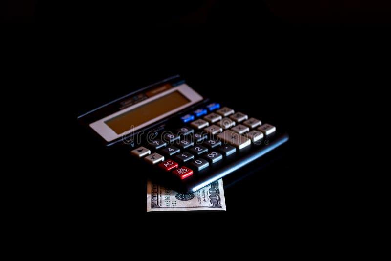 Uitgavenkosten, begroting en belasting of investeringsberekening, dollar honderd met calculator op donkere zwarte lijst als achte stock afbeeldingen