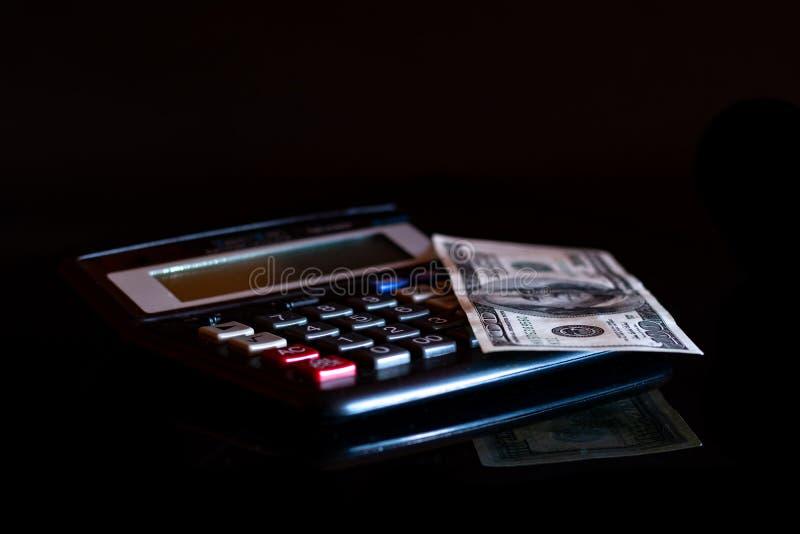 Uitgavenkosten, begroting en belasting of investeringsberekening, dollar honderd met calculator op donkere zwarte lijst als achte stock fotografie