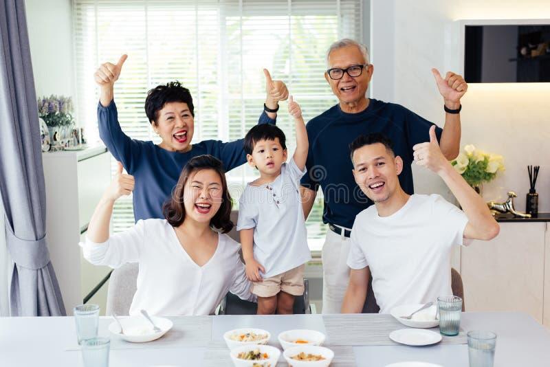 Uitgebreide Aziatische familie van drie generaties die een maaltijd hebben togethe stock foto