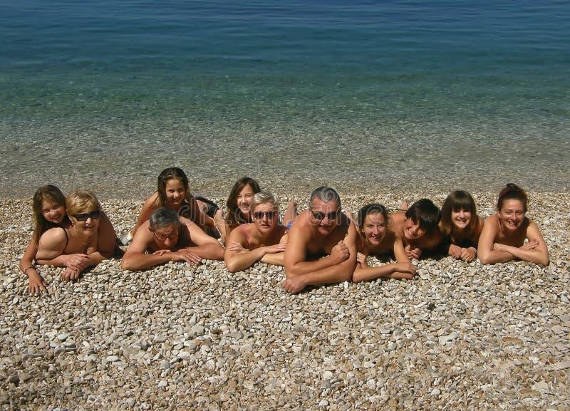 Uitgebreide familie bij strand stock foto's